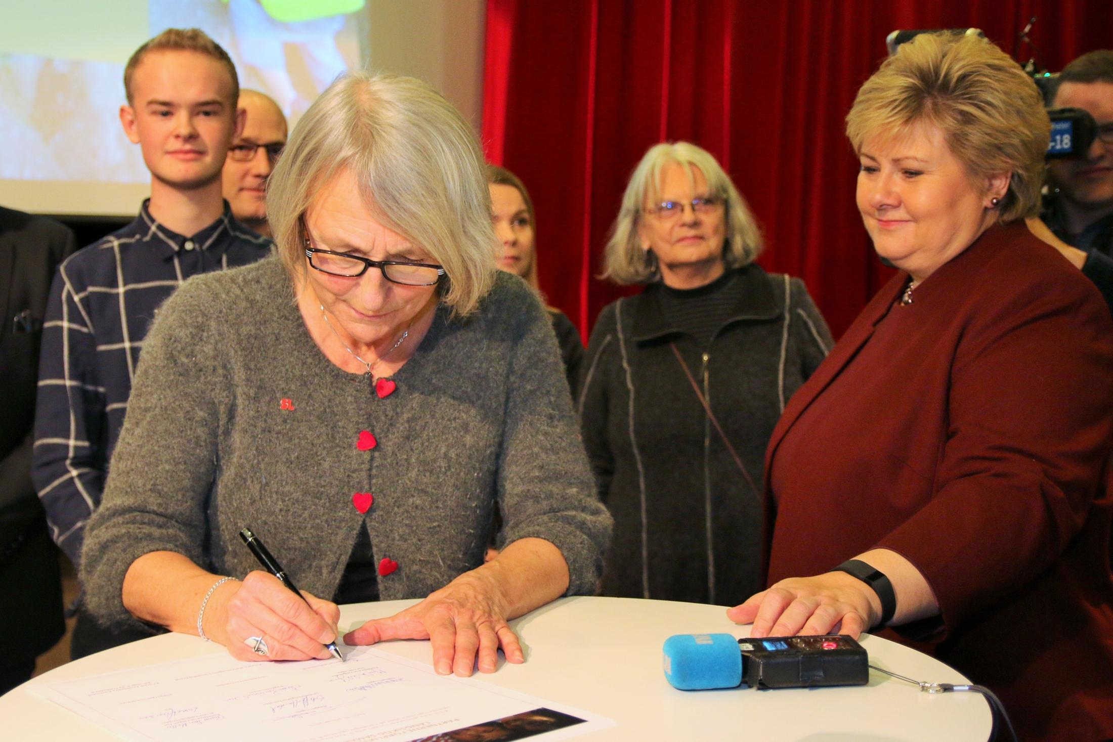 SL-leder Anne Finborud signerer et nytt Partnerskap mot mobbing, på Marienlyst skole i Oslo. Statsminister Erna Solberg (H) følger nøye med. (Foto: SL)